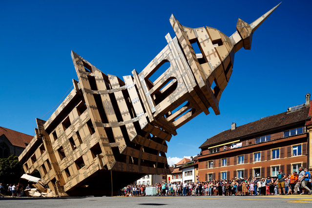 """A cardboard tower with a height of 20 meters and a weight over a tone is brought down during the street festival """"Les Jeux du castrum"""" in Yverdon-les-Bains, Switzerland, 13 August 2017. The piece and performance designed by French artist Olivier Grossetete has brought back to life a replica of the former 19th century """"Tour de la Plaine"""" tower from Yverdon-les-Bains. (Photo by Valentin Flauraud/EPA)"""