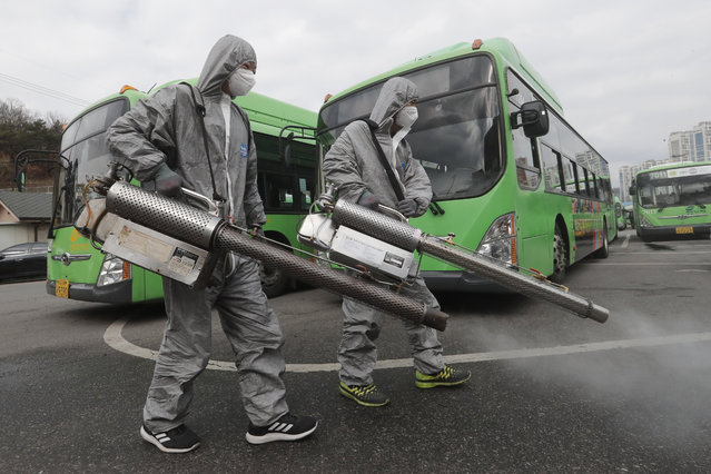 Workers wearing protective suits spray disinfectant as a precaution against the coronavirus at a bus garage in Seoul, South Korea, Wednesday, February 26, 2020. The number of new virus infections in South Korea jumped again Wednesday and the U.S. military reported its first case among its soldiers based in the Asian country, with his case and many others connected to a southeastern city with an illness cluster. (Photo by Ahn Young-joon/AP Photo)