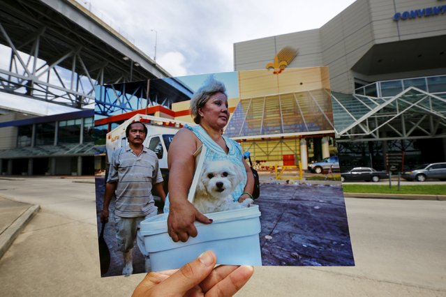 Photographer Carlos Barria holds a print of a photograph he took in 2005, as he matches it up at the same location 10 years on, in New Orleans, United States, August 17, 2015. The print shows a woman arriving with her dog at a collection point for victims of Hurricane Katrina, September 8, 2005. (Photo by Carlos Barria/Reuters)