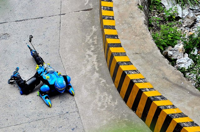 French roller man Jean-Yves Blondeau slides down a corner at Tianmen Mountain in Zhangjiajie, in south China's Hunan province on July 22, 2012. Blondeau, inventor of the 31-wheel roller suit, also known as the wheel suit, succeeded in his attempt to navigate the 10.77 km road featuring 99 U-turns, finishing the course in19 mins 34 sec. (Photo by Associated Press)