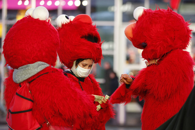 A mask-wearing costumed character in Times Square looks through bills during a lull in activity Thursday, March 12, 2020, in New York. Earlier Thursday, Gov. Andrew Cuomo banned gatherings of 500 or more people. (Photo by Kathy Willens/AP Photo)