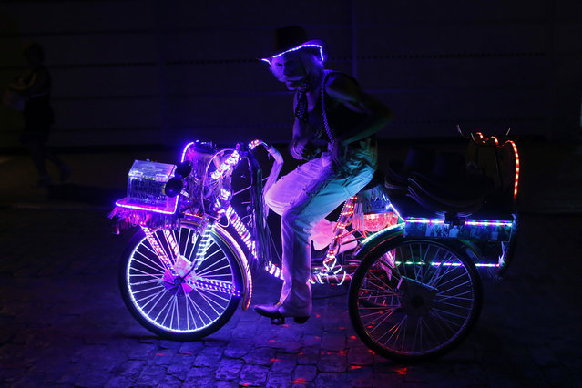 A man poses on a tricycle near the site during the Feast of the La Paloma Virgin in Madrid late August 15, 2014. (Photo by Javier Barbancho/Reuters)