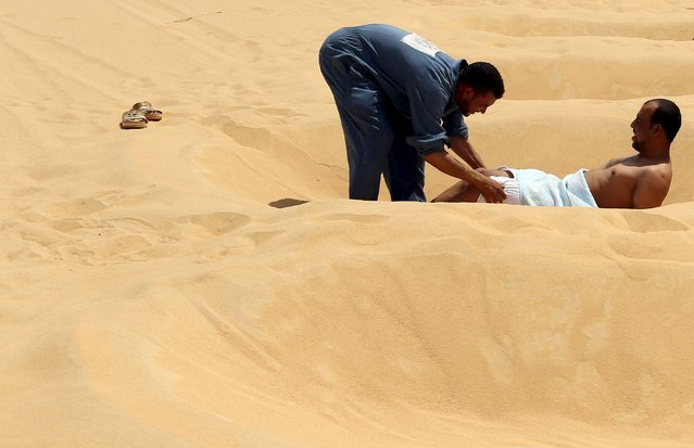 A worker helps a patient take off his clothes before he's buried in the sand in Siwa, Egypt, August 11, 2015. (Photo by Asmaa Waguih/Reuters)