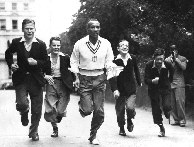 Olympic gold medalist Jesse Owens finds himself the object of extreme interest on the part of a group of boys, as he trots back to his quarters through Hyde Park in London, August 19, 1936. (Photo by AP Photo)