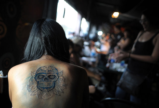 A woman takes a rest as she has her back tattooed during the San Salvador Tattoo Fest in San Salvador, on March 3, 2012. The tattoo festival aimed to promote tattoo art in the rather conservative Salvadorean society. (Photo by Jose Cabezas/AFP)