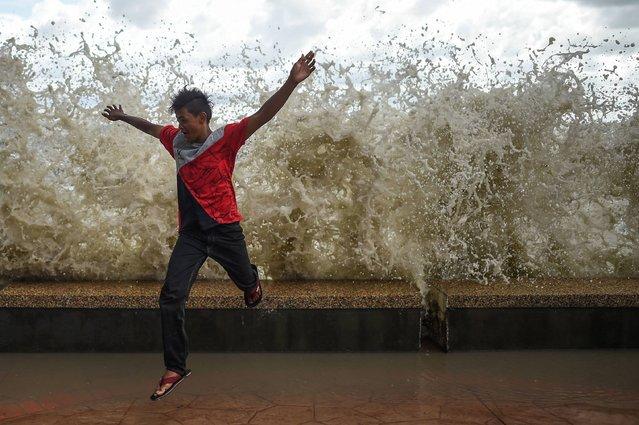 A Malaysian boy runs away from a high wave at Morib Beach in Banting, outside Kuala Lumpur on July 18, 2016. (Photo by Mohd Rasfan/AFP Photo)