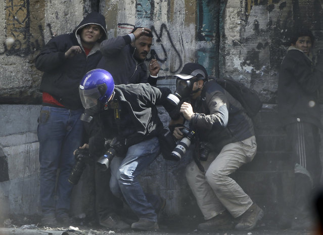 Photographers cower as protesters throw stones towards riot police along Sheikh Rihan street near Tahrir Square in Cairo January 25, 2013. (Photo by Amr Abdallah Dalsh/Reuters)