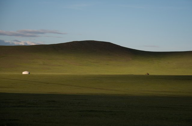 A man rides his horse next to a ger near Zuunmod south of Ulan Bator on June 29, 2016. Mongolians went to the polls across their sprawling, sparsely-populated country on June 29 as it struggles to benefit from its vast natural resources amid disputes over foreign investment and slumping demand from neighbouring China. It took Mongolian nomad Pagvajaviin Shatarbaatar seven days to get to his polling station to vote in in the general election – accompanied by more than 2,000 sheep, goats and horses. (Photo by Johannes Eisele/AFP Photo)