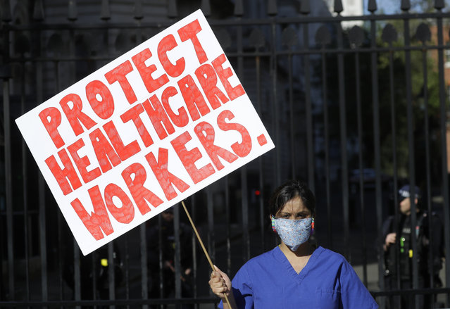 In this April 19, 2020, file photo, Dr. Meenal Viz holds a banner as she protests outside the prime minister's residence on Downing Street in London as the country continues its lockdown to help curb the spread of the coronavirus. Hospital organizations are lambasting Britain's government for failing to give medical staff the appropriate clothing and equipment needed to deal with the COVID-19 outbreak. Viz staged a one-woman protest on Sunday to express her dismay. (Photo by Kirsty Wigglesworth/AP Photo/File)