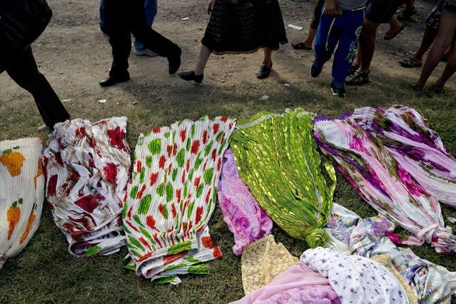 People walk by traditional Roma skirts on sale as the Roma community celebrates the Birth of the Virgin Mary in Costesti, Romania, Monday, September 8, 2014. (Photo by Vadim Ghirda/AP Photo)