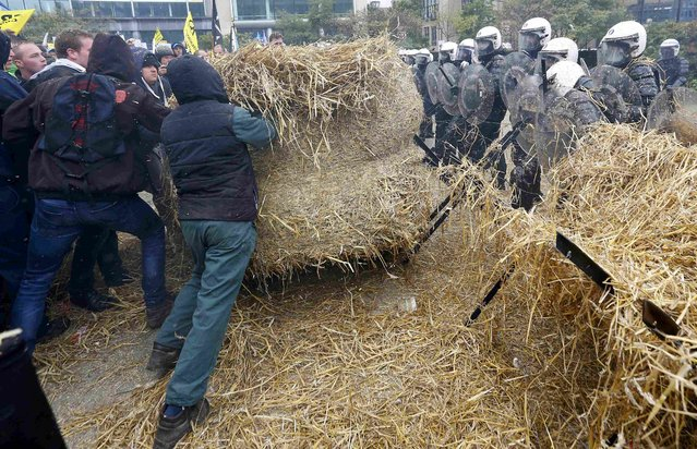Belgian riot police officers stand guard while protesters push an hay ball as farmers and dairy farmers from all over Europe take part in a demonstration outside an European Union farm ministers emergency meeting at the EU Council headquarters in Brussels, Belgium, September 7, 2015. (Photo by Yves Herman/Reuters)