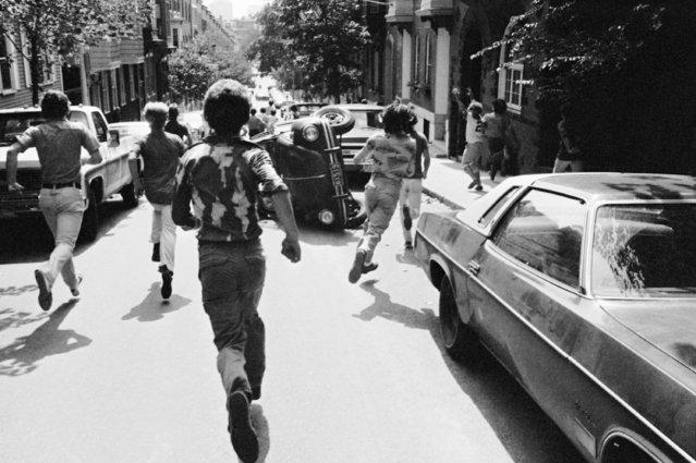 Youths run through streets of Boston's Charlestown section past car overturned by roving gangs on Monday, September 8, 1975 in Boston. Isolated incidents marred the opening of Boston schools under Phase 2 of the court-ordered desegregation program. (Photo by AP Photo)
