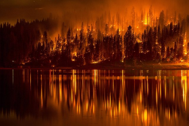 This Sunday, Sept. 14, 2014 photo shows fire as it approaches the shore of Bass Lake, Calif. Crews are attempting to get better access to two raging wildfires in California Monday that have forced hundreds to evacuate their homes. (AP Photo/YosemiteLandscapes.com. Darvin Atkeson)