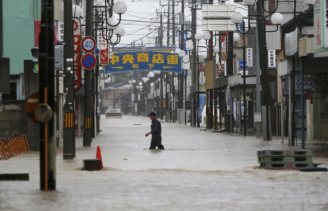 A man wades through a local shopping area flooded by the Kinugawa river, caused by typhoon Etau, in Joso, Ibaraki prefecture, Japan, September 10, 2015. One person was missing on Thursday as 90,000 people were ordered to evacuate after rivers burst their banks in cities north of Tokyo following days of heavy rain pummelling Japan, according to local media. (Photo by Issei Kato/Reuters)