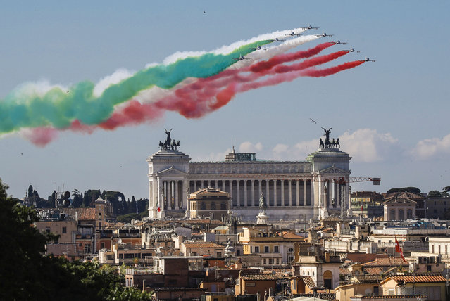 The Frecce Tricolori (Tricolor Arrows) aerobatic squad of the Italian Air Force fly over Rome and the Unknown Soldier monument, visible in foreground, Tuesday, June 2, 2020, as part of the celebrations for the 74th anniversary of the Italian Republic born on June 2, 1946. (Photo by Alessandra Tarantino/AP Photo)