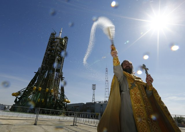 An Orthodox priest conducts a blessing in front of the Soyuz TMA-14M spacecraft set on the launch pad at Baikonur cosmodrome September 24, 2014. (Photo by Shamil Zhumatov/Reuters)