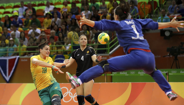 Brazil's Eduarda Taleska, left, scores a goal past Montenegro's Marina Rajcic, right, as Montenegro's Jovanka Radicevic, center, looks on during the women's preliminary handball match between Brazil and Montenegro at the 2016 Summer Olympics in Rio de Janeiro, Brazil, Sunday, August 14, 2016. (Photo by Ben Curtis/AP Photo)