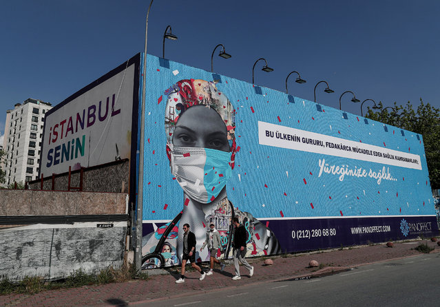 People wearing face masks walk by in front of a billboard set up to support health workers, amid the ongoing pandemic of the COVID-19 disease caused by the SARS-CoV-2 coronavirus, in Istanbul, Turkey, 28 May 2020. (Photo by Sedat Suna/EPA/EFE/Rex Features/Shutterstock)