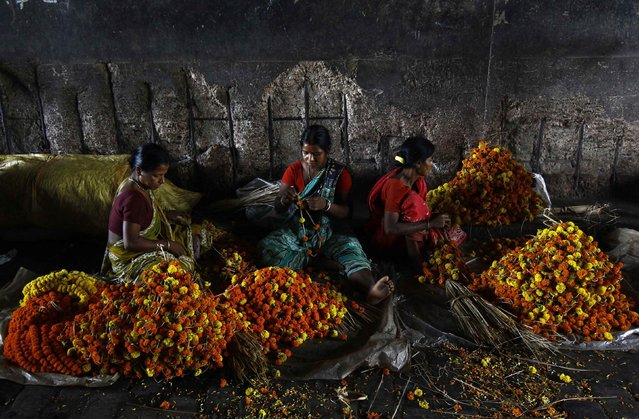 Workers make garlands of marigold flowers at a wholesale flower market ahead of the Durga Puja festival in Kolkata September 29, 2014. The Durga Puja festival will be celebrated from September 30 to October 3, and is the biggest religious event for Bengali Hindus. Hindus believe that the goddess Durga symbolises power and the triumph of good over evil. (Photo by Rupak De Chowdhuri/Reuters)