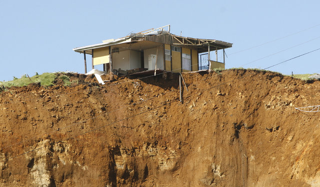 A house sits at the edge of a hill after a landslide caused by an earthquake in San Rafael de Vara Blanca, north of San Jose, January 10, 2009. (Photo by Roger Benavides/Reuters)