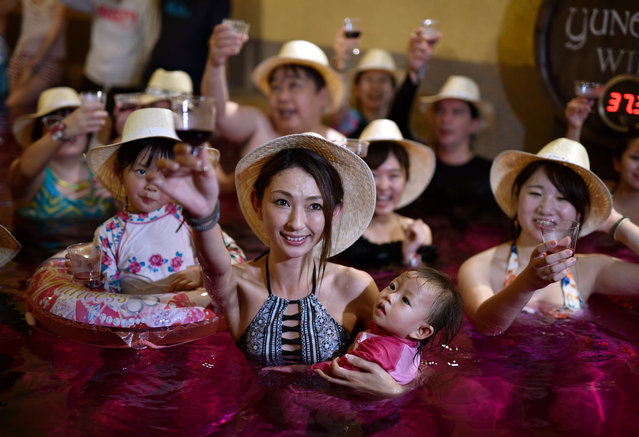 """A mother raise her glass filled with 2017 Beaujolais Nouveau wine as she holds her child in a colored hot water """"wine bath"""" at Hakone Kowakien Yunessun hot spring resort in Hakone, west of Tokyo, Japan, 16 November 2017, on the day of the Beaujolais Nouveau official release. With Germany and the United States, Japan is a major market for the Beaujolais Nouveau. (Photo by  Franck Robichon/EPA/EFE)"""