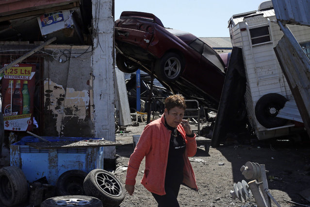 A woman walks past a car, propped up in mid-air, among the debris left behind by an earthquake-triggered tsunami in the coastal town of Coquimbo, Chile, Thursday, September 17, 2015. Several coastal towns were flooded from small tsunami waves set off by late Wednesday's quake, which shook the Earth so strongly that rumbles were felt across South America. (Photo by Luis Hidalgo/AP Photo)