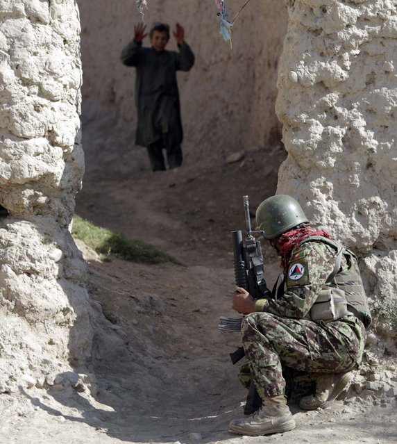 An Afghan soldier of 215th Maiwand Corps takes up position in an alley during a joint patrol with U.S. marines of Fox Co, 2nd Battalion, 7th Marines Regiment in a village at Musa Qal-Ah district in Helmand province, southwestern Afghanistan on November 1, 2012. (Photo by Erik De Castro/Reuters Photo)