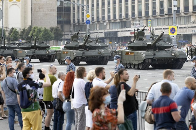 In this file photo taken on Wednesday, June 17, 2020, people, same of them wearing face a masks, glasses and gloves to protect against the coronavirus watch as Russian military vehicles roll along Tverskaya street toward Red Square during a rehearsal for the Victory Day military parade in Moscow, Russia. A massive military parade that was postponed by the coronavirus will roll through Red Square this week to celebrate the 75th anniversary of the end of World War II in Europe, even though Russia is continuing to register a steady rise in infections. (Photo by Alexander Zemlianichenko/AP Photo/File)