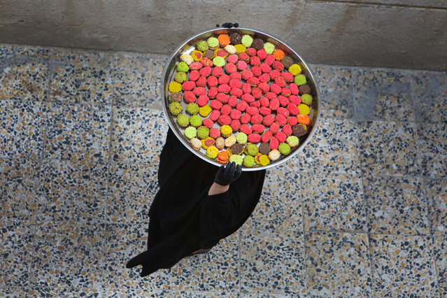 An Iraqi women carries cookies for the upcoming Muslim Eid al- Fitr celebrations, that marks the end of the Muslim holy fasting month of Ramadan, in Basra, Iraq, Friday, May 22, 2020. (Photo by Nabil al-Jurani/AP Photo)