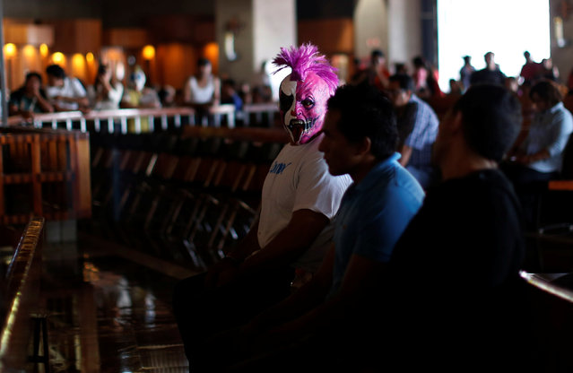 Mexican wrestler known as Psycho sits inside the Basilica of Our Lady Guadalupe during the annual pilgrimage in Mexico City, Mexico August 25, 2016. (Photo by Carlos Jasso/Reuters)