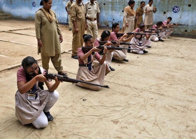 Girls practise with rifles during a weapons training course at the firing range of the police headquarters in Ahmedabad August 12, 2014. (Photo by Amit Dave/Reuters)