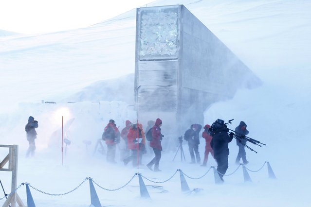 Journalists and cameramen walk under a gust of cold wind near the entrance of the Svalbard Global Seed Vault that was officially opened near Longyearbyen on February 26, 2008. A vault carved into the Arctic permafrost and filled with samples of the world's most important seeds was inaugurated Tuesday, providing a Noah's Ark of food crops in the event of a global catastrophe. (Photo by Hakon Mosvold Larsen/AFP Photo)