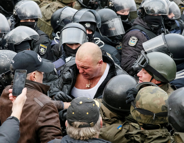 A supporter of former Georgian president Mikheil Saakashvili clashes with riot police in Kiev, Ukraine, Tuesday, December 5, 2017. Once freed, Saakashvili raised a hand in a V-for-victory sign – a handcuff still dangling from his wrist as he stood in a melee of supporters. He then led protesters towards parliament, where he called defiantly for President Petro Poroshenko to be removed from office. (Photo by Gleb Garanich/Reuters)