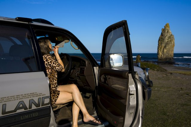 A woman applies lipstick in a car that is parked at a beach facing a volcanic rock called Devil's Finger outside Yuzhno-Kurilsk, the main settlement on the Southern Kurile island of Kunashir September 15, 2015. (Photo by Thomas Peter/Reuters)