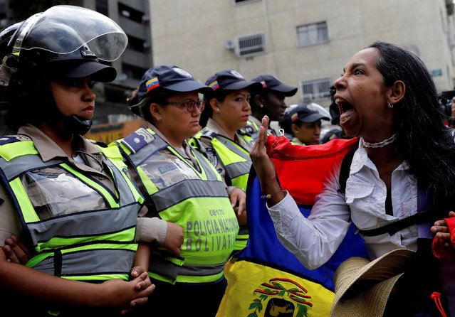 """A demonstrator shouts slogans in front of police officers during a women's march to protest against President Nicolas Maduro's government in Caracas, Venezuela May 6, 2017. The women's marches, which took place in most major cities around the country, were the latest in five weeks of sustained protests against Maduro. In Caracas, marchers sang the national anthem and shouted 'We want elections!'. They were halted at various points by lines of policewomen and National Guard troops with armoured cars. Carlos Garcia Rawlins: """"Unlike most of the previous protests, after many hours the protesters decided to leave and there were no violent clashes"""". (Photo by Carlos Garcia Rawlins/Reuters)"""