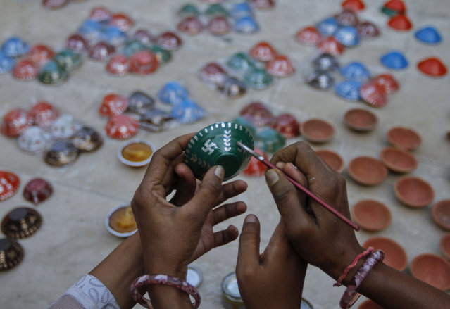 """Visually impaired girls from the Andh Kalyan Kendra prepare wax-filled earthen lamps or """"Kodiyas"""" for the forthcoming Diwali festival, the festival of lights – in Ahmedabad, October 18, 2011. (Photo by Amit Dave/Reuters)"""