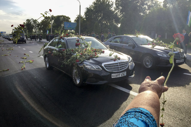 People throw flowers on limousines as they gather along a road to watch the funeral procession of President Islam Karimov in Tashkent, Uzbekistan, early Saturday, September 3, 2016. Karimov has died of a stroke at age 78, the Uzbek government announced Friday. (Photo by Umida Akhmedova/AP Photo)