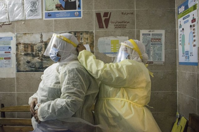 A nurse helps a colleague to put on her personal protective equipment at the 6th of October Central Hospital, which is currently serving as an isolation hospital for coronavirus (COVID-19) patients in Giza, Egypt on July 7, 2020. Photo by Menna Hossam/picture alliance via Getty Images)