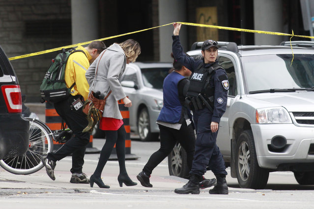A Ottawa police officer holds up a length of police tape for pedestrians leaving the downtown area following shooting incidents in Ottawa October 22, 2014. (Photo by Blair Gable/Reuters)