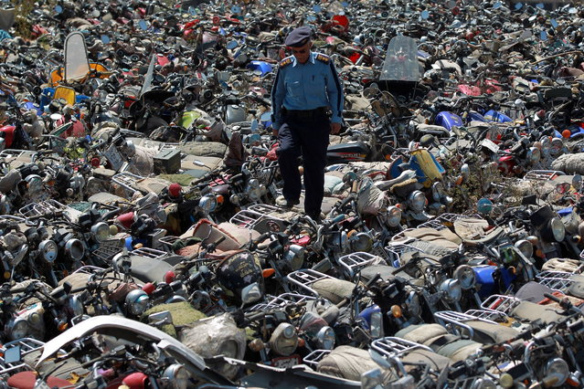 A Yemeni policeman walks on motorcycles that were seized after their owners violated a ban on motorcycles on October 20, 2014, at the police headquarters in the capital Sanaa. Yemen began the day before enforcing a temporary ban on motorcycles in the capital to prevent blasts or attacks. (Photo by Mohammed Huwais/AFP Photo)