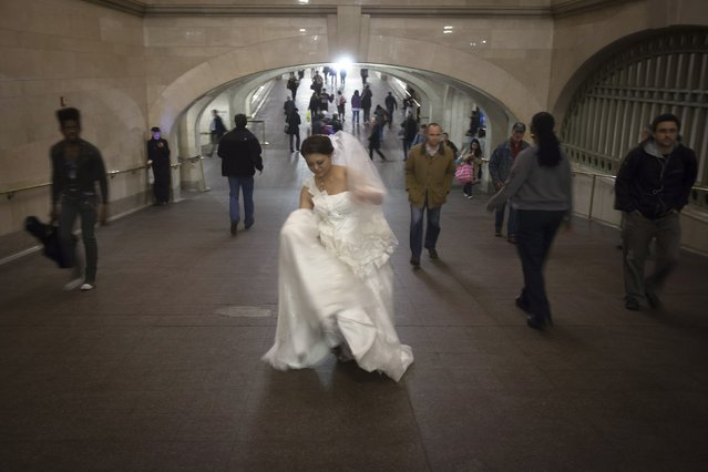 A bride walks though Grand Central Terminal in New York October 24, 2014. (Photo by Carlo Allegri/Reuters)