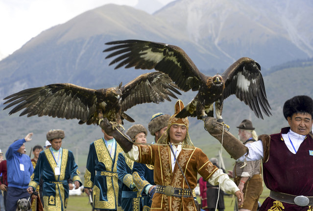 In this photo taken on Sunday, September 4, 2016, participants hold golden eagles for an eagle hunt during the second World Nomad Games at Issyk Kul lake in Cholpon-Ata, Kyrgyzstan. (Photo by Vladimir Voronin/AP Photo)