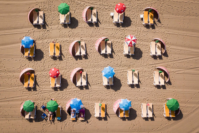 An image taken with a drone shows beach umbrellas and deck chairs as beachgoers enjoy the hot weather in Scheveningen, the Netherlands, 24 July 2019. The Royal Dutch Meteorological Institute has issued an official warning due to high temperatures affecting the country as well as Western Europe. (Photo by Sem van der Wal/EPA/EFE)