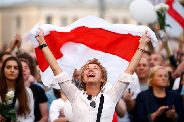A demonstrator reacts while holding the historical white-red-white flag of Belarus during an opposition demonstration to protest against police violence and to reject the presidential election results near the Government House in Independence Square in Minsk, Belarus on August 14, 2020. (Photo by Vasily Fedosenko/Reuters)