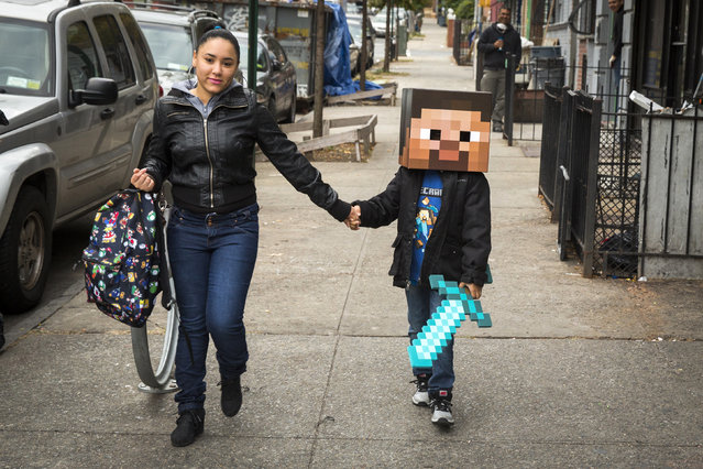 A woman walks her child to school as he is dressed as a character from Minecraft in New York, October 31, 2014. (Photo by Lucas Jackson/Reuters)