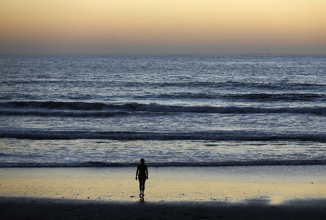 A woman walks out of the ocean following a swim past sunset at Moon Light Beach in Encinitas, California October 28, 2014. (Photo by Mike Blake/Reuters)