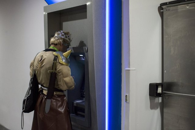 A man dressed as a character from Clash of Clans mobile game uses at an ATM at the New York Comic Con in Manhattan, New York, October 8, 2015. (Photo by Andrew Kelly/Reuters)