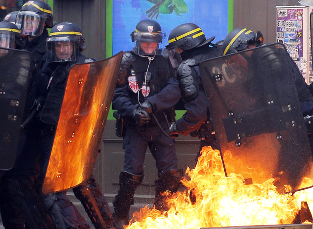 Leftist protesters throw a petrol bomb at riot policemen during clashes in Paris, France, Thursday, September 15, 2016. (Photo by Christophe Ena/AP Photo)