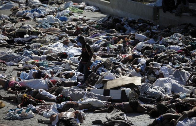 A man looks for a body among hundreds of earthquake victims at the morgue in Port-au-Prince, Thursday, January 14, 2010. A 7.0-magnitude  earthquake struck Haiti Tuesday. (Photo by Ariana Cubillos/AP Photo)
