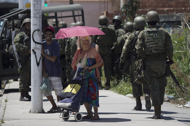 A line of soldiers file past residents during a surprise operation in the Manguinhos slum in Rio de Janeiro, Brazil, Thursday, January 18, 2018. (Photo by Leo Correa/AP Photo)